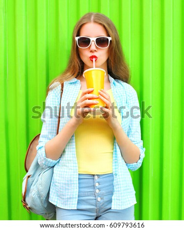 Fashion young woman is drinking fruit juice from cup over colorful green background #609793616