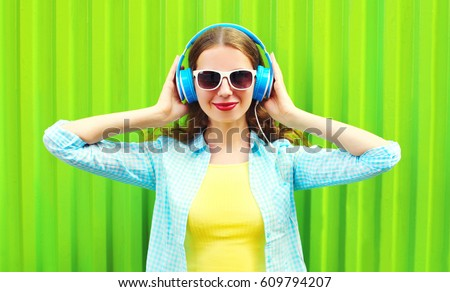 Fashion portrait smiling young woman listens to music in headphones over green colorful background #609794207