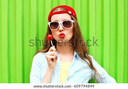 Fashion portrait pretty woman with lollipop candy over green colorful background #609794849
