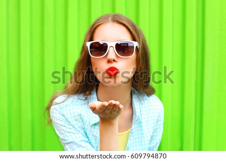 Fashion portrait pretty woman in white sunglasses sends an air kiss over colorful green background #609794870