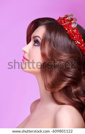 Beautiful brunette woman with long Curly hair wearing crown decorated gemstones. Fashion makeup and hairstyle. Portrait of young gorgeous bride. Isolated on pink background #609801122