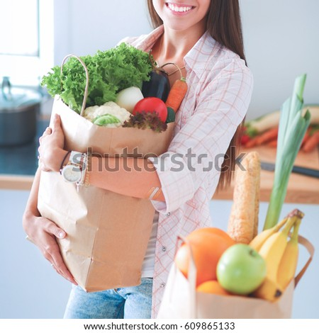 Young woman holding grocery shopping bag with vegetables  #609865133