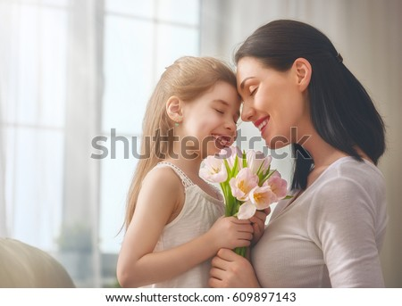 Happy mother's day! Child daughter congratulates mom and gives her flowers tulips. Mum and girl smiling and hugging. Family holiday and togetherness. #609897143