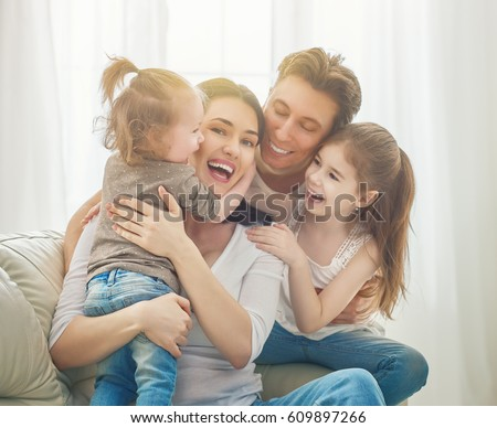 Happy mother's day! Two children daughters with father congratulate mom. Mum, dad and girls laughing and hugging. Family holiday and togetherness. #609897266