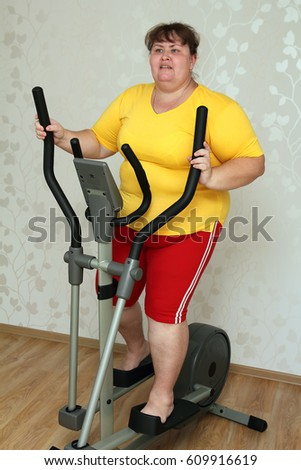 overweight woman exercising on trainer ellipsoid #609916619