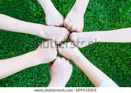 Business team hands joining together over green yard background, business teamwork, cooperation success in business concept #609933059