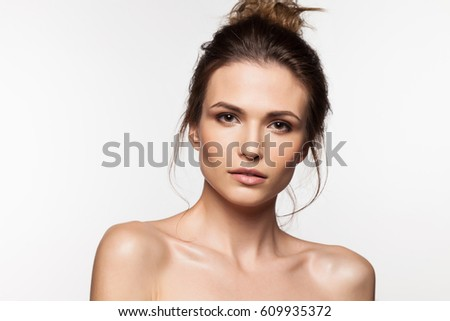 Brunette woman with bare shoulders, with clean skin and natural make-up on a white background #609935372