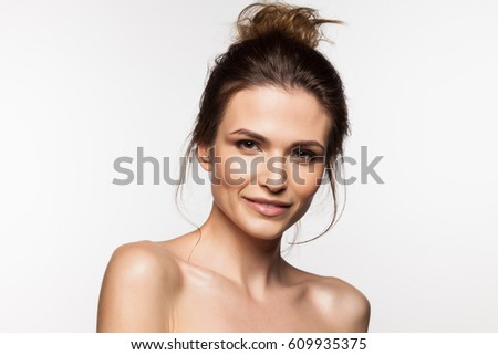 Smiling woman with bare shoulders, with clean skin and natural make-up on a white background #609935375