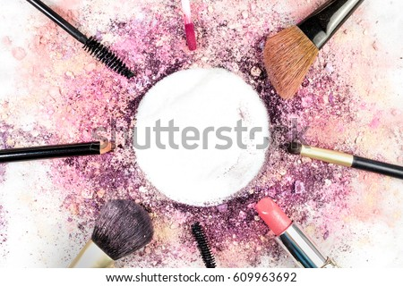 Makeup brushes, pencil, lipstick and other objects, forming a frame on a light background, with crushed powder and copy space. A horizontal template for a makeup artist's business card or flyer design