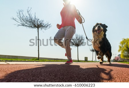 Young pretty girl running outdoor in the spring with her Bernese Mountain dog Royalty-Free Stock Photo #610006223