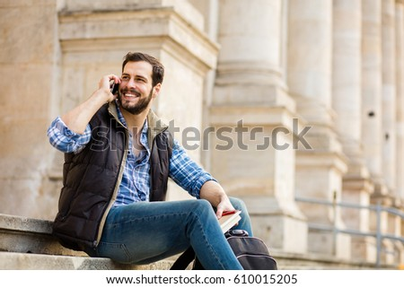 smiling young man sitting on stairs outside in front of classical big building and talking on cell-phone #610015205