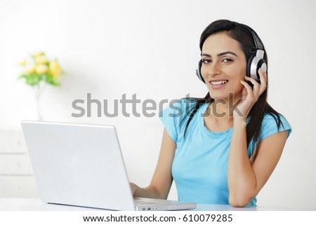 Portrait of beautiful young woman with laptop listening to headphones at home  #610079285