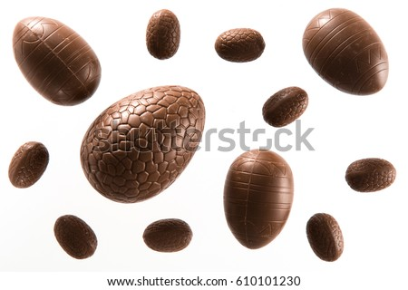 High angle view of a variety of unwrapped Easter chocolate eggs on a white background  Royalty-Free Stock Photo #610101230