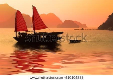 Junk boat at sunset in Halong Bay, Vietnam Royalty-Free Stock Photo #610106255