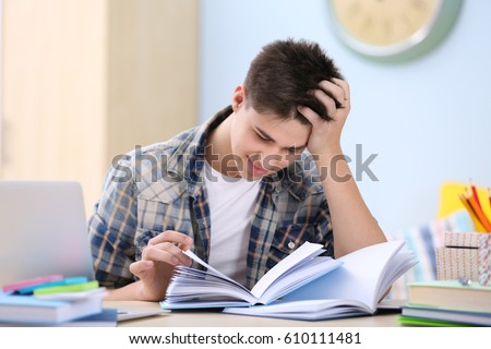 Teenager sitting at table and studying at home #610111481