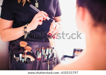 Makeup artist doing makeup for girl indoor Royalty-Free Stock Photo #610155797