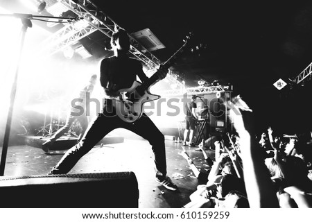 Guitarist on a stage playing rock to the crowd of people. black and white Royalty-Free Stock Photo #610159259