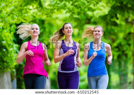 Three motivated women jogging in green forest #610212545