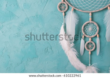 Mint cream dream catcher on turquoise textured background. Texture of concrete.  Royalty-Free Stock Photo #610222961