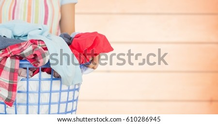 Digital composite of Woman in apron with laundry against blurry orange wood panel #610286945