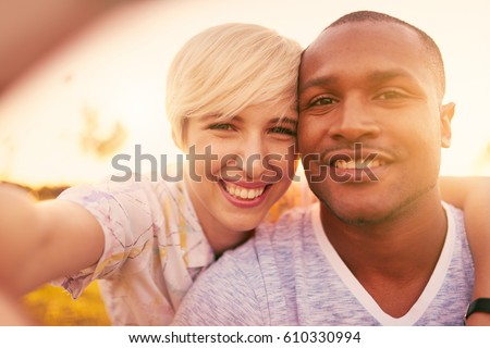 Mixed race couple of millennial in a grass field taking a selfie with a smartphone #610330994