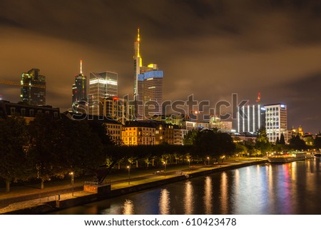 Night view of the skyline of Frankfurt am Main from the Holbeinsteg bridge with the skyscrapers and modern buildings, Hesse, Germany #610423478