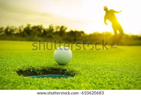 Golfer action to win after long putting golf ball on the green golf. sunset time.