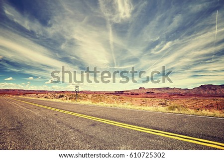 Vintage toned picture of a scenic desert road. #610725302