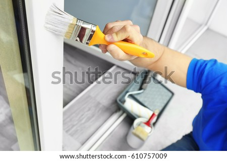 Young man painting window at home, closeup Royalty-Free Stock Photo #610757009