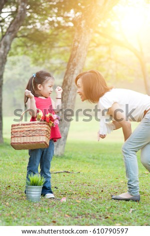 Lifestyle portrait mom and daughter in happiness at the outside in the meadow, family outdoor fun, morning with sun flare. #610790597