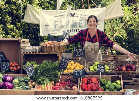 Greengrocer selling organic fresh agricultural product at farmer market Royalty-Free Stock Photo #610807595