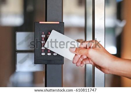 Door access control - young woman holding a key card to lock and unlock door. Royalty-Free Stock Photo #610811747