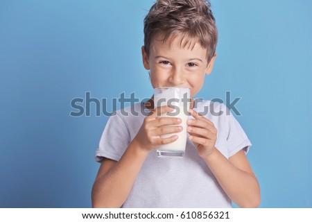 Cute kid drinking milk on blue background #610856321
