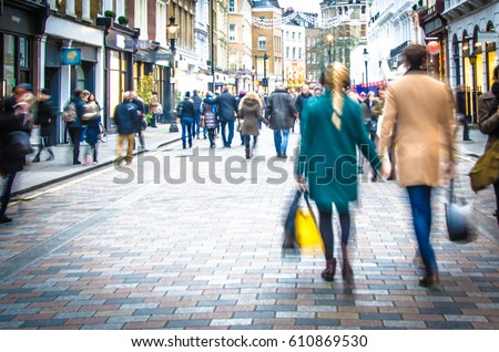 Shoppers holding hands in busy London high street #610869530