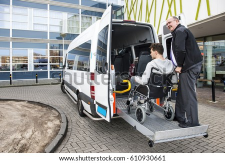 The driver of a wheel chair taxi, helping a disabled man in a wheel chair, using the lift in the back of his mini van #610930661