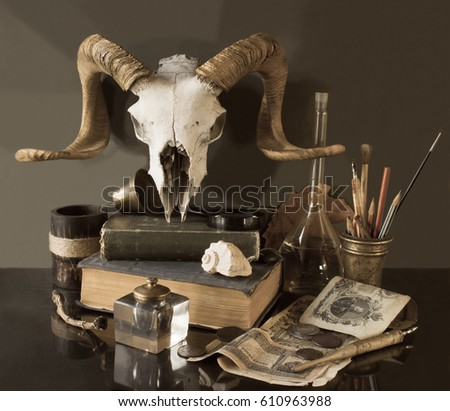 Still life with a skull, books, inkwell, paper, magnifier, candle,  shell on a dark background #610963988