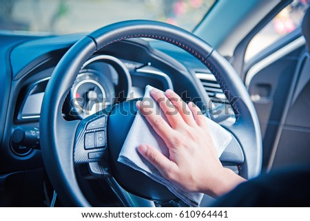 Hand cleaning the car interior with gray microfiber cloth  #610964441