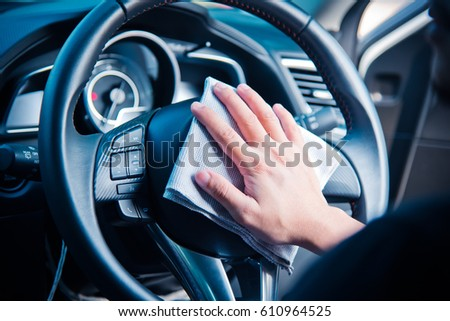 Hand cleaning the car interior with gray microfiber cloth  #610964525
