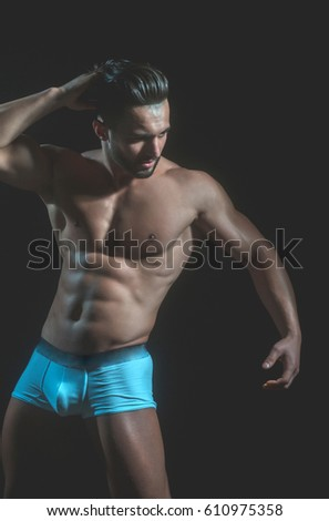 handsome muscular macho man or athlete guy with sexy body of bodybuilder with torso, belly, six packs, has beard on serious face in white pants isolated on black background #610975358