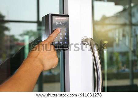 Close-up hand pressing keyword to lock and unlock door - Door access control keypad with keycard reader Royalty-Free Stock Photo #611031278