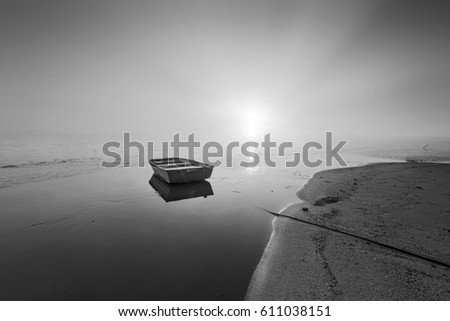 Long exposure shot of single boat at the beach. Black and white photography.