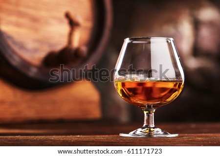 Glass of Cognac and old oak barrel defocussed Royalty-Free Stock Photo #611171723
