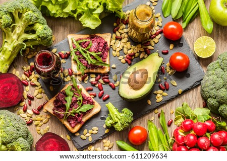 Healthy vegan food. Fresh vegetables on wooden background. Detox diet. Different colorful fresh juices. Royalty-Free Stock Photo #611209634