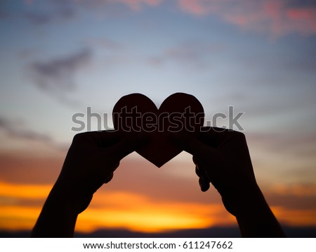 silhouette hand is raising the red paper heart with blur sunlight during sunset, Valentines day Royalty-Free Stock Photo #611247662