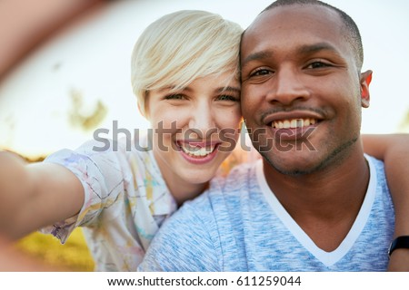 Mixed race couple of millennial in a grass field taking a selfie with a smartphone #611259044