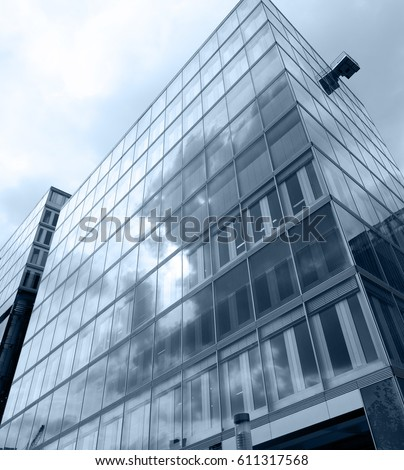 A modern glass fronted building  with the sky and clouds  #611317568