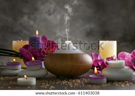 Aroma oil diffuser, candles and flowers on table Royalty-Free Stock Photo #611403038