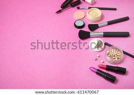 Make up and cosmetic beauty products arranged on a bright pink background, with blank space at side #611470067