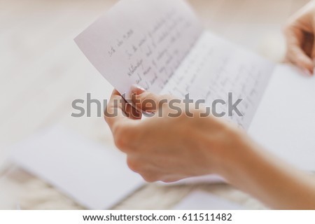 Hands of young woman holding handwritten letter  Royalty-Free Stock Photo #611511482