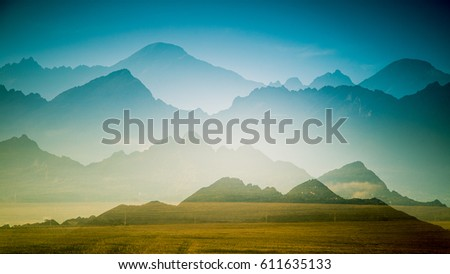 A beautiful, colorful, abstract mountain landscape with a hot summer haze in warm green tonality. Decorative, artistic double exposure. #611635133